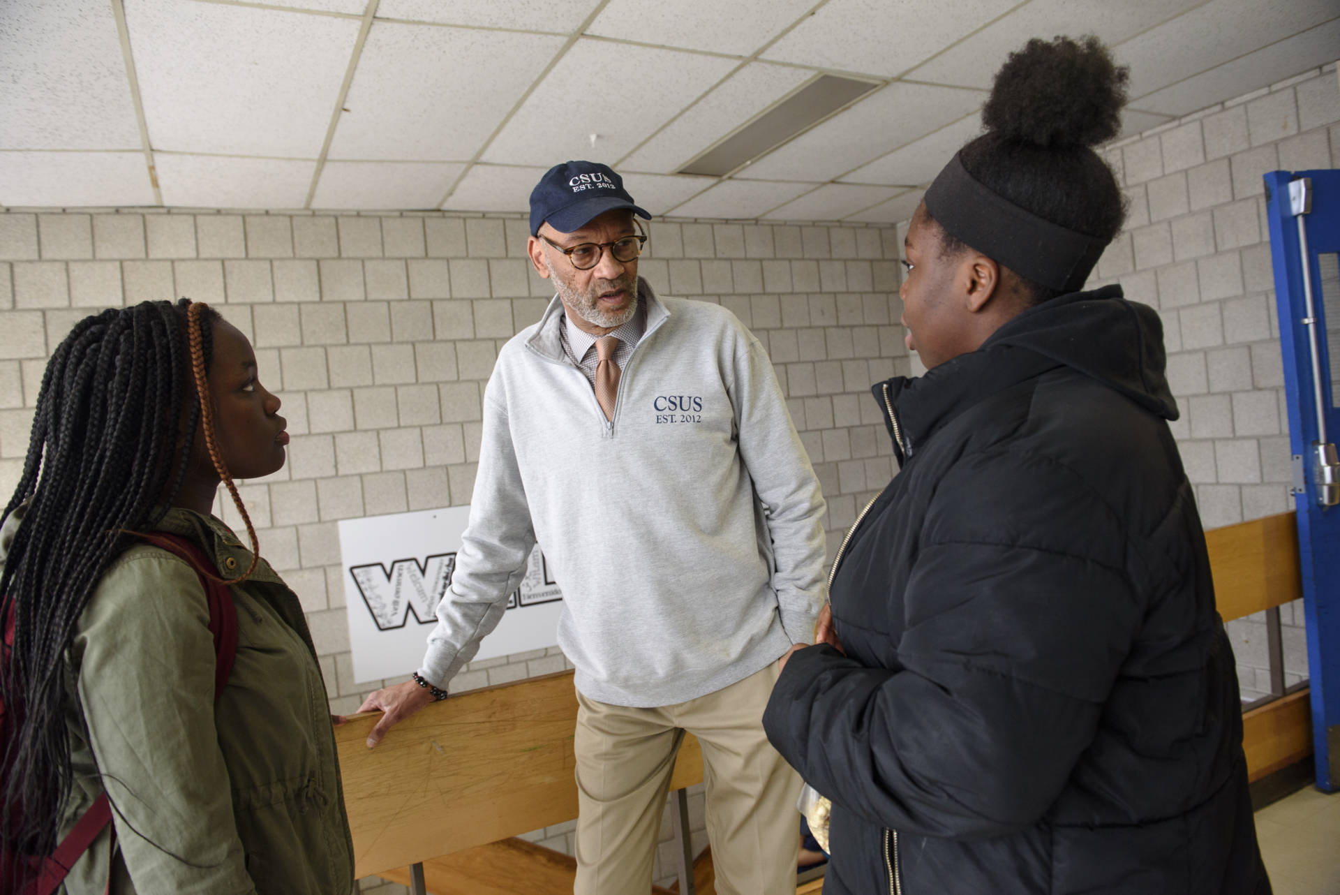 Cambridge Street Upper School principal Manuel J. Fernandez talks with students between classes, March 29, 2019, in Cambridge, MA.