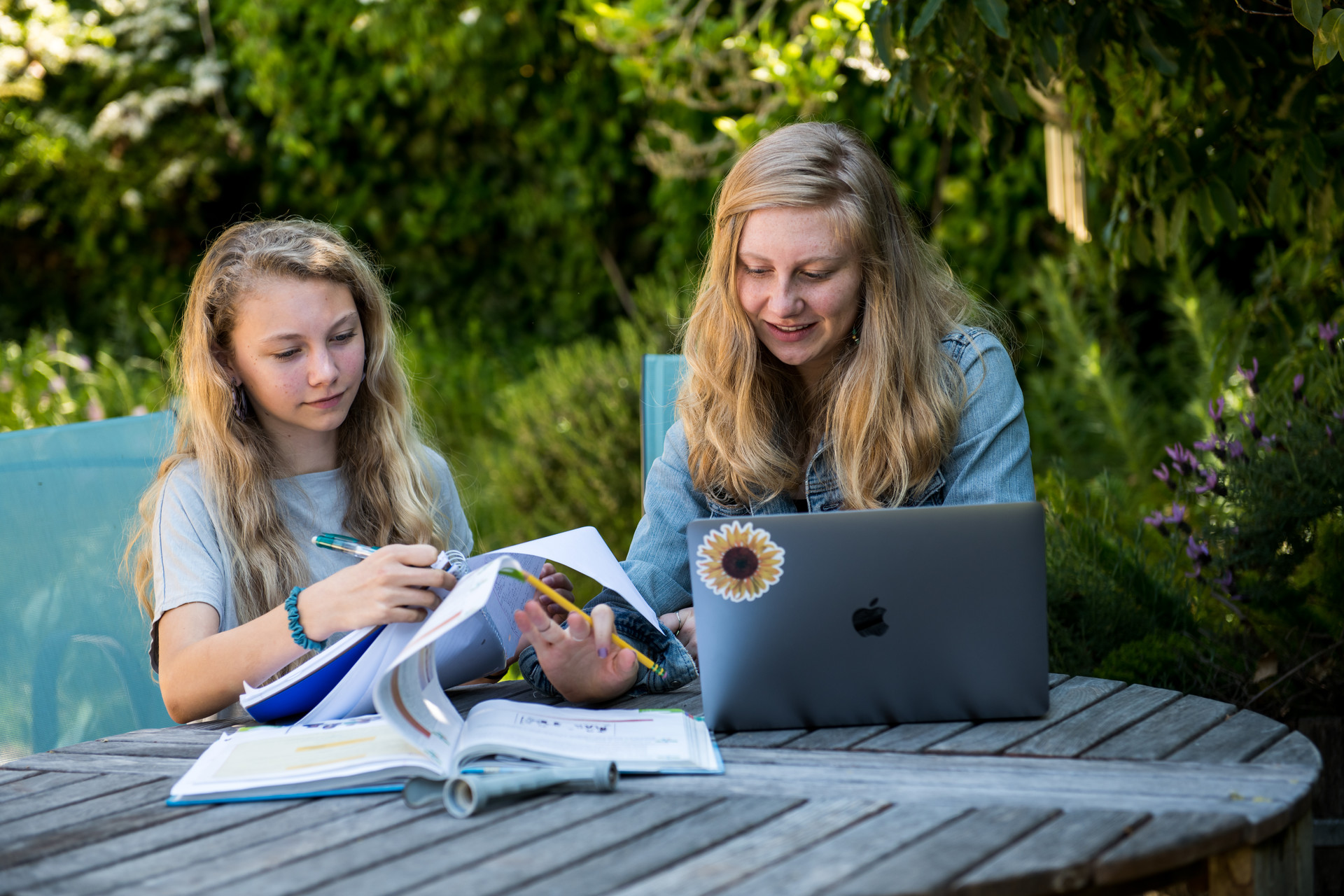 Genevieve Schweitzer and her sister, Julia, study in their backyard.