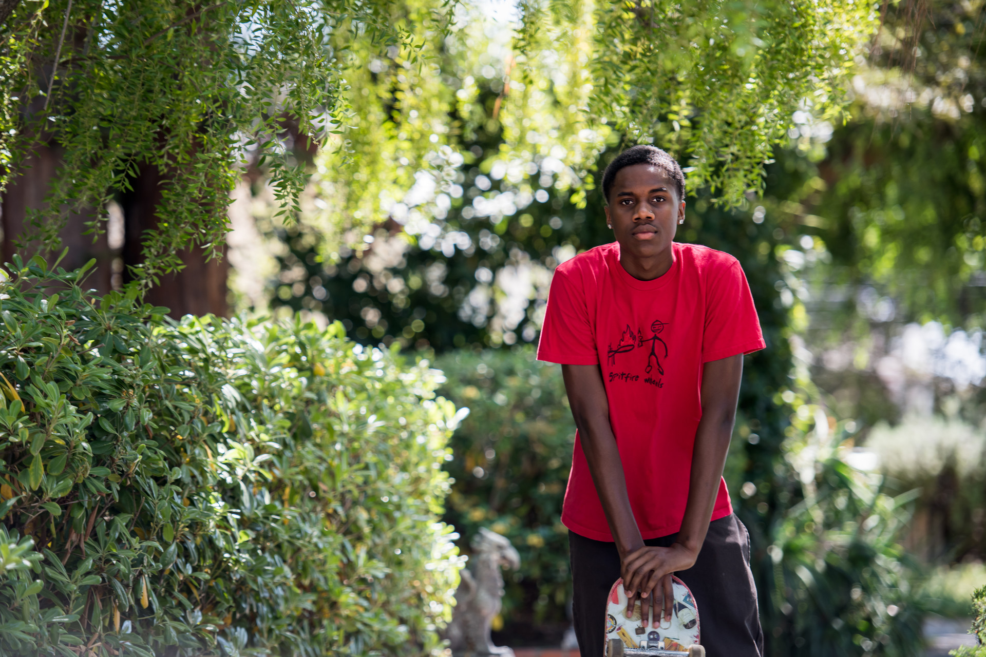 Qadir Scott, a senior at Oakland Technical High school, leans on his skateboard.