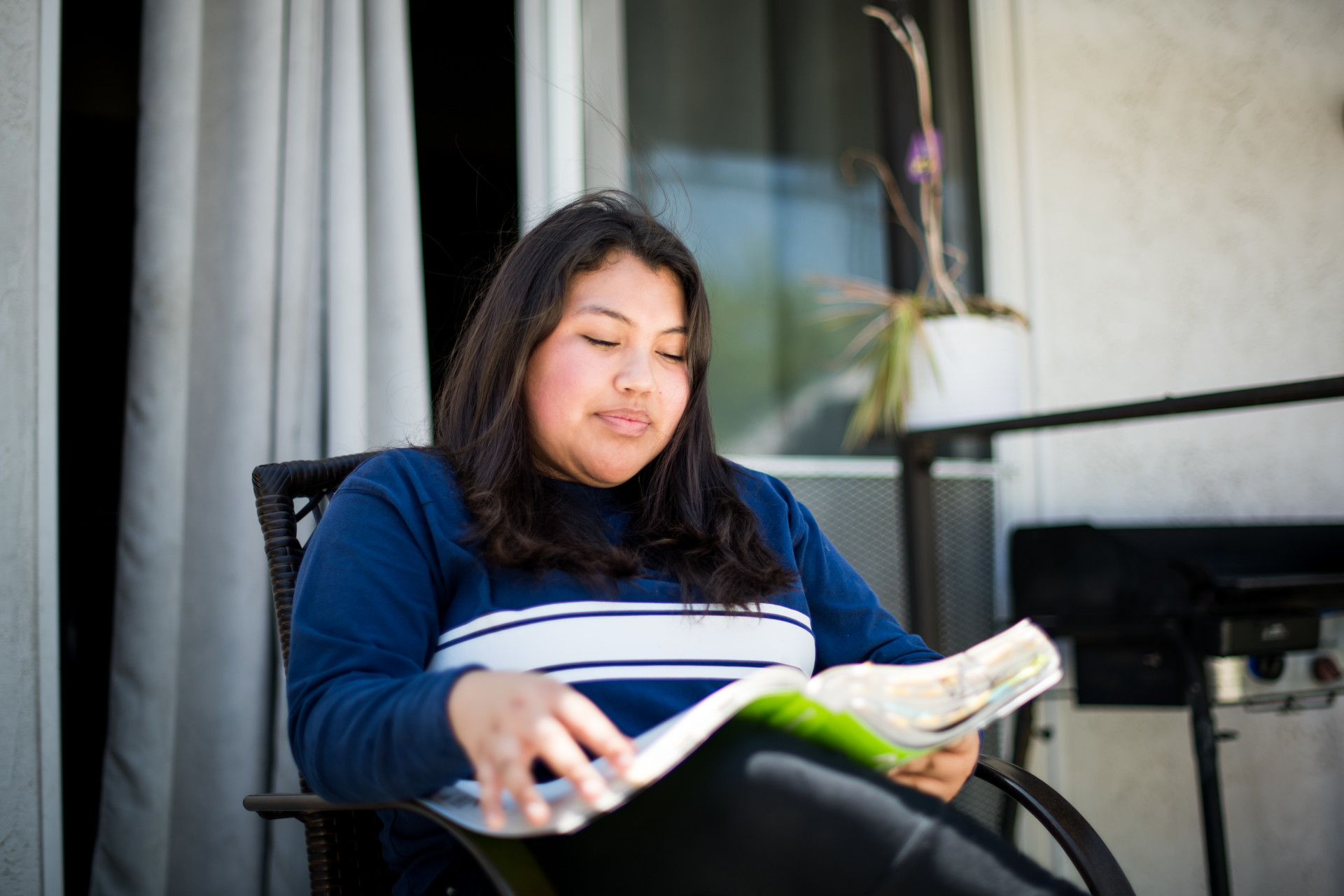 Julisa Gomez Reyes, a high school junior, stuides in her backyard.
