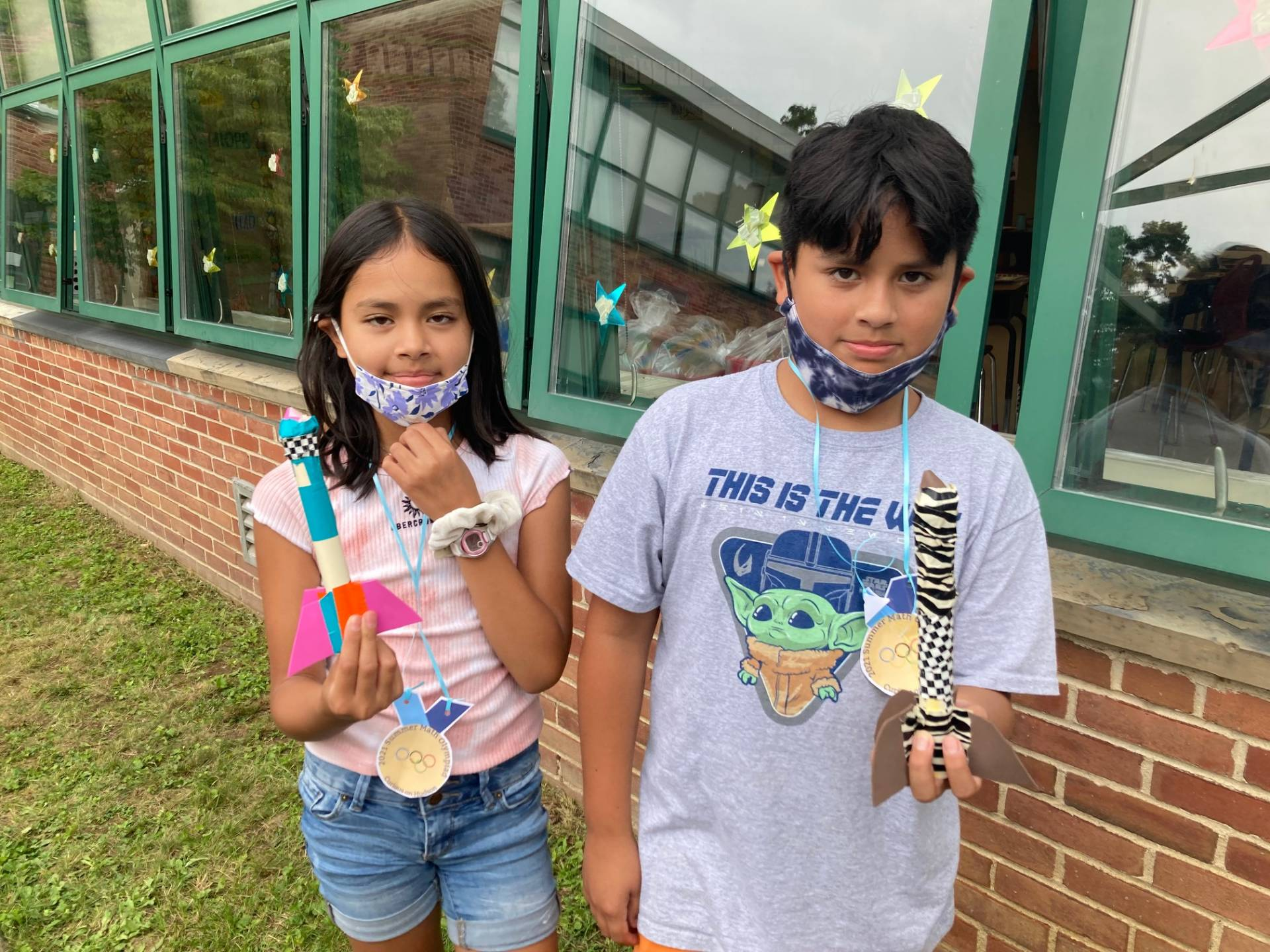 Two students display their rockets prior to launch.