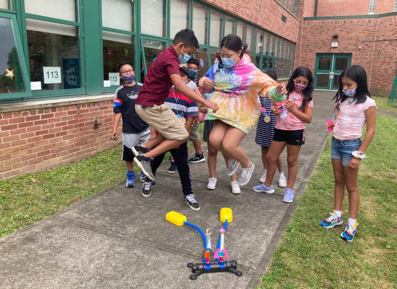 Students jump on pump to propel their rockets into the air