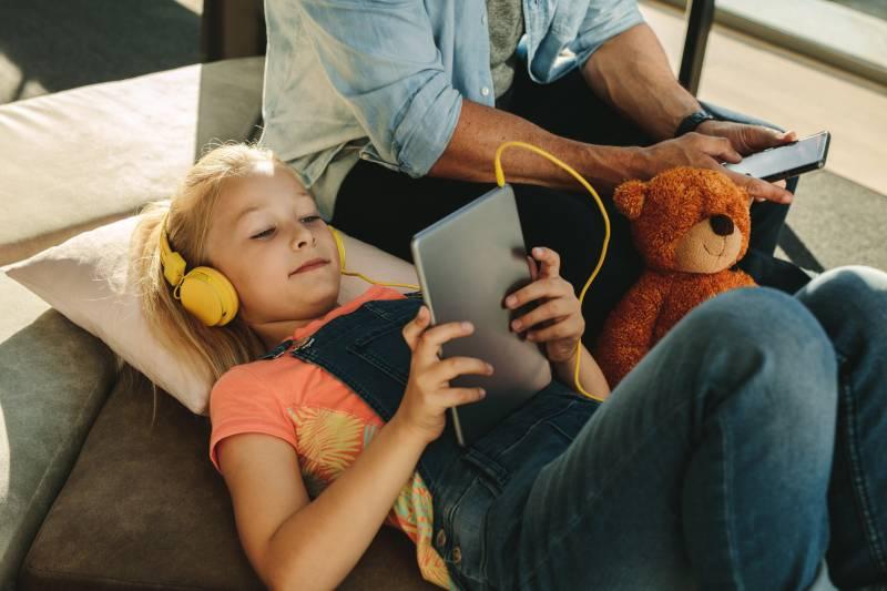 Girl on iPad alongside parent