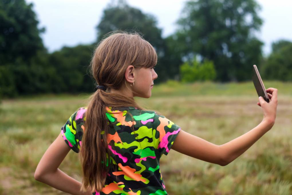 Girl taking selfie at a park