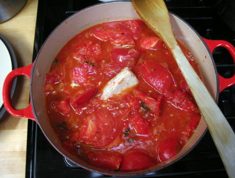 Parm rind in a pot of stewed tomatoes, later to be strained for a soup