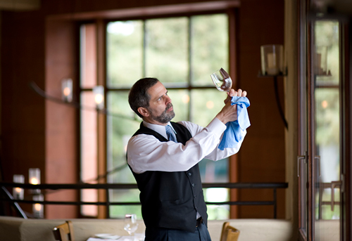 Server Eric Schwier puts a shine on one of the workmanlike wine glasses at Oliveto.