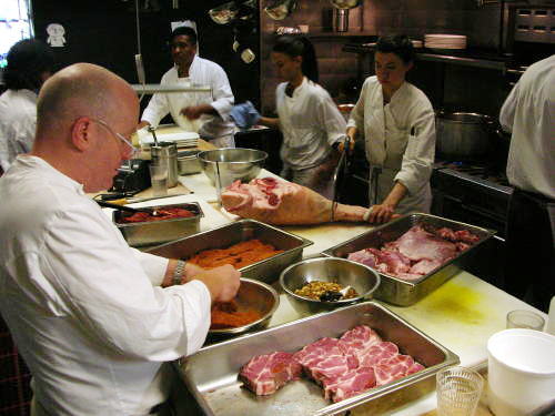Oliveto Chef Paul Canales seasons pork cutlets while Sous Chef Kelsey Bergstrom cuts into a pork leg with a hand saw.