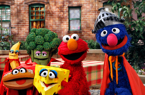 Elmo and Super Grover pose with the four healthy food groups (Fruits, Vegetables, Dairy, and Grains) as part of Sesame Street's Food For Thought initiative. Copyright 2010 Sesame Workshop.  Photo by: Richard Termine.