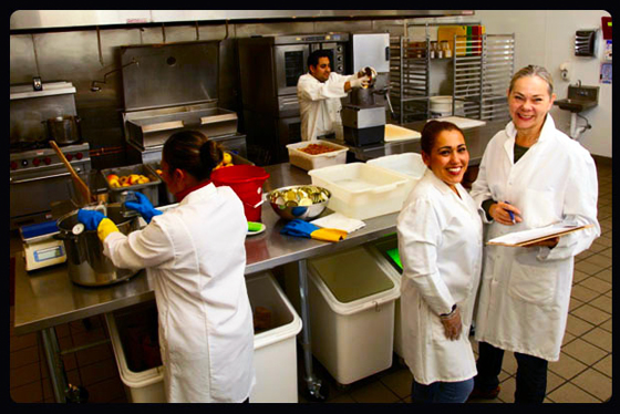 Merrilee Olson, on right, and her crew in the FoodWorks kitchen.