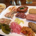 Pate platter with pickled items, mustard, caper berries and cornichons