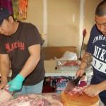 The men in the family cut up the pig in garage in preparation for the feast.