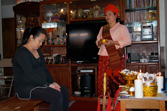A Hmong shaman blesses a young pregnant woman in rural Merced