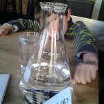 Mary Ladd's son behind H2O beaker at Chocolate Lab