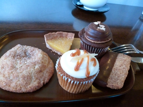 """An assortment of Sweet Bar sweets: Front row: snickerdoodle, pumpkin ginger cupcake, """"the sweet bar"""" (chocolate-dipped almond shortbread) Back row: slice of lemon tart, chocolate peanut butter cupcake"""