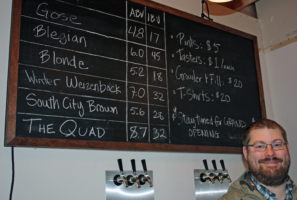 Nick Armstrong with the blackboard of beers available on tap in the tasting room at Armstrong Brewing Co. in South San Francisco.