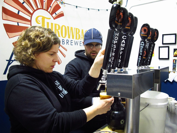 Throwback Brewery co-owner Nicole Carrier and assistant brewer Chris Naro pour beer for customers at their North Hampton, N.H., taproom. Photo: Emily Corwin/NHPR