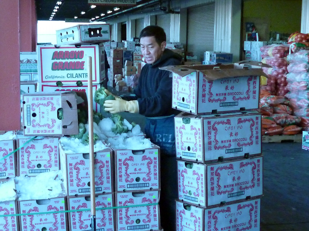 Produce worker with boxes of broccoli