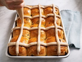 "The Bouchon Bakery cookbook demonstrates how to apply the frosting ""cross"" on a pan of hot cross buns. Photo: Deborah Jones/Artisan Books"