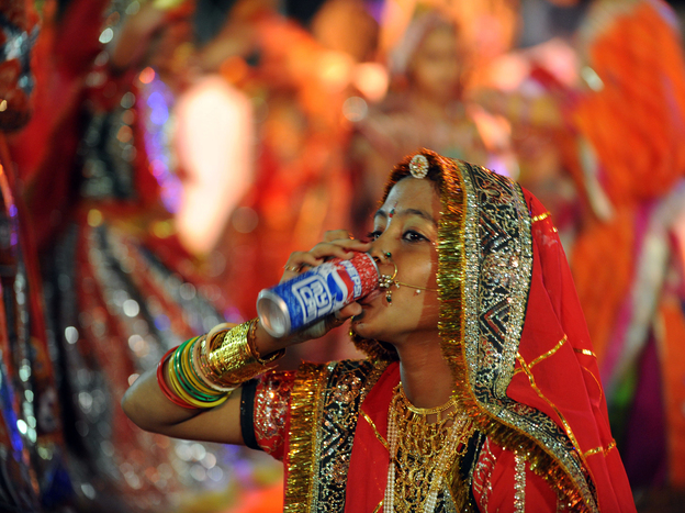 A performer drinks a soda in Ahmedabad, India in 2010. A study found that rising diabetes prevalence in countries like India is strongly tied to sugar consumption. Photo: Sam Panthaky/AFP/Getty Images
