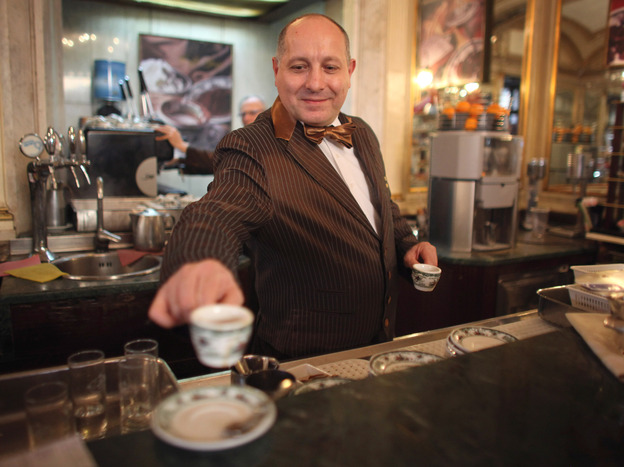 A barista serves coffee at a cafe in Naples, Italy. The Italian city's long-standing tradition of buying a cup for a less-fortunate stranger is now spreading across Europe. Photo: Christopher Furlong/Getty Images