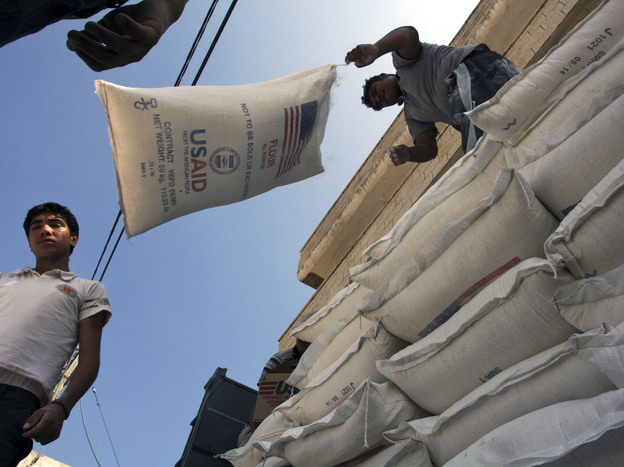 Palestinians unload bags of flour donated by USAID, or the United States Agency for International Development, at a depot in the West Bank village of Anin near Jenin, in 2008. Photo: Mohammed Ballas/AP