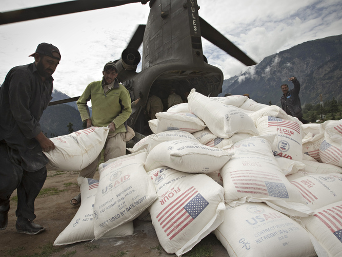 Pakistani aid workers offload USAID food supplies from an Army helicopter in Kallam Valley during catastrophic flooding in 2010. Photo: Behrouz Mehri/AFP/Getty Images