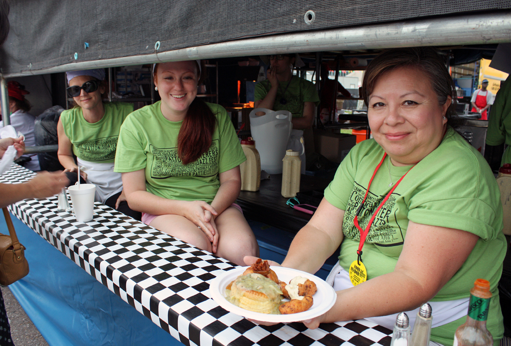 Christine Christy, Haley Marquette and Olga Marquette of Patton's Caterers serve a combo plate with crawfish beignets, crawfish sack and oyster patties. Credit: Tilde Herrera