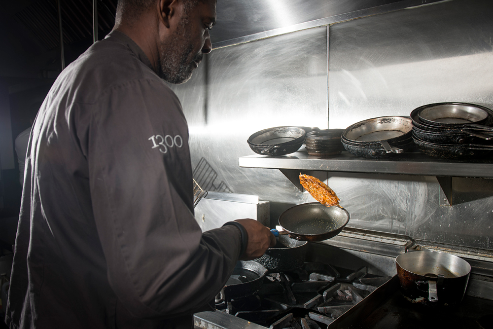 Chef David Lawrence flipping a caramelized onion, yam-potato rosti (pancake). Photo courtesy of 1300 on Fillmore