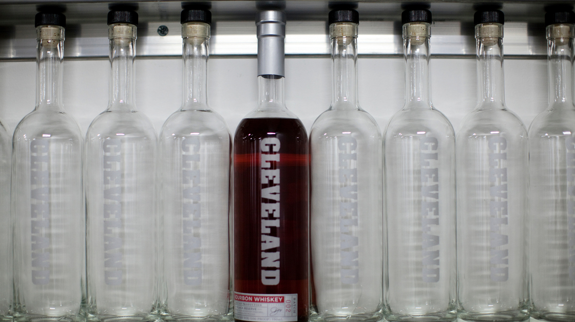 A bottle of Cleveland Whiskey's bourbon sits on a shelf with empty bottles at the company's distillery. Photo: David Kidd
