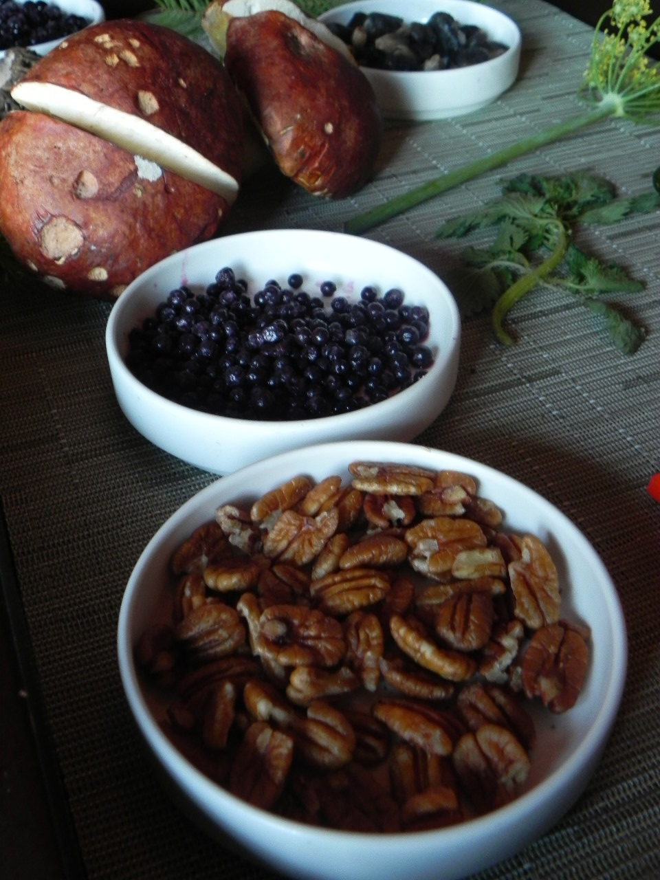 A display of the various edibles Stewart found in the Sierra Nevada. From bottom to top: a bowl of wild pecans, elderberries, Sierra porcinis and huitlacoche which he describes as corn infected with fungus.