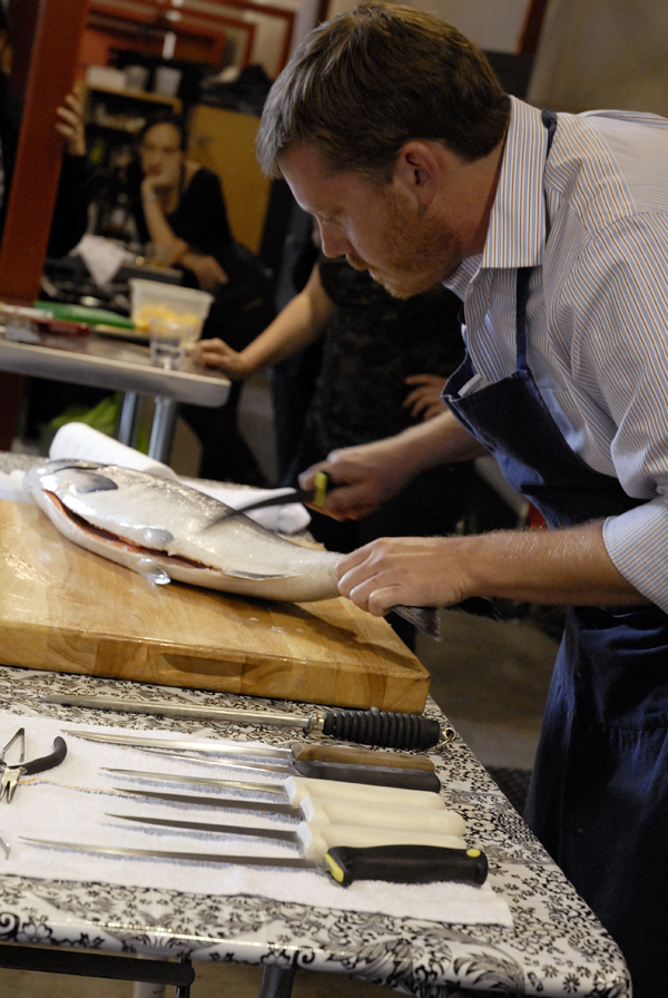 Chef Neil Davidson removing scales from a whole salmon. Photo: Wendy Goodfriend