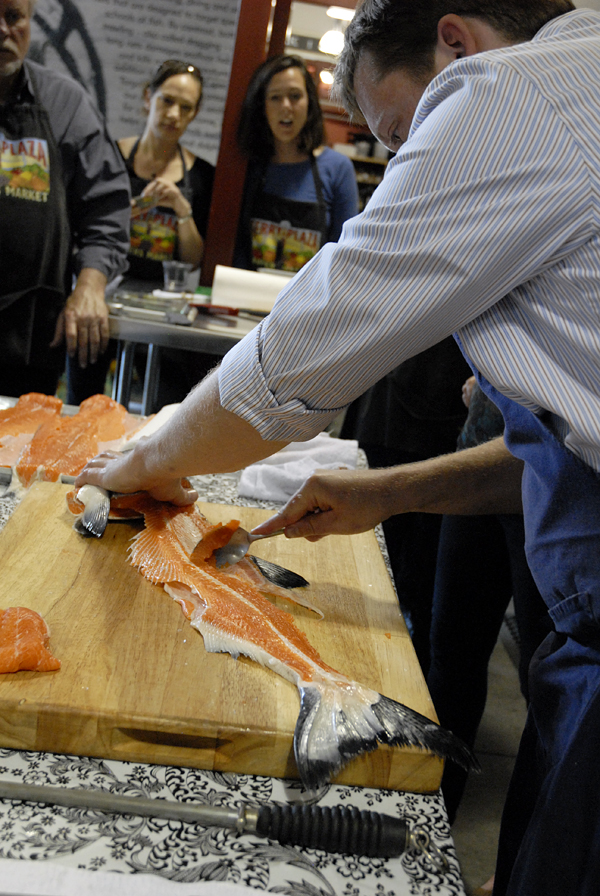 Chef Neil Davidson uses a spoon to scrape remains of salmon from bones to use for fish patties. Photo: Wendy Goodfriend