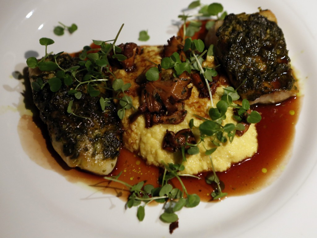 Fillets of chimichurri-crusted red snapper and tilapia, separated by fresh corn polenta. Photo: Heather Rousseau/NPR