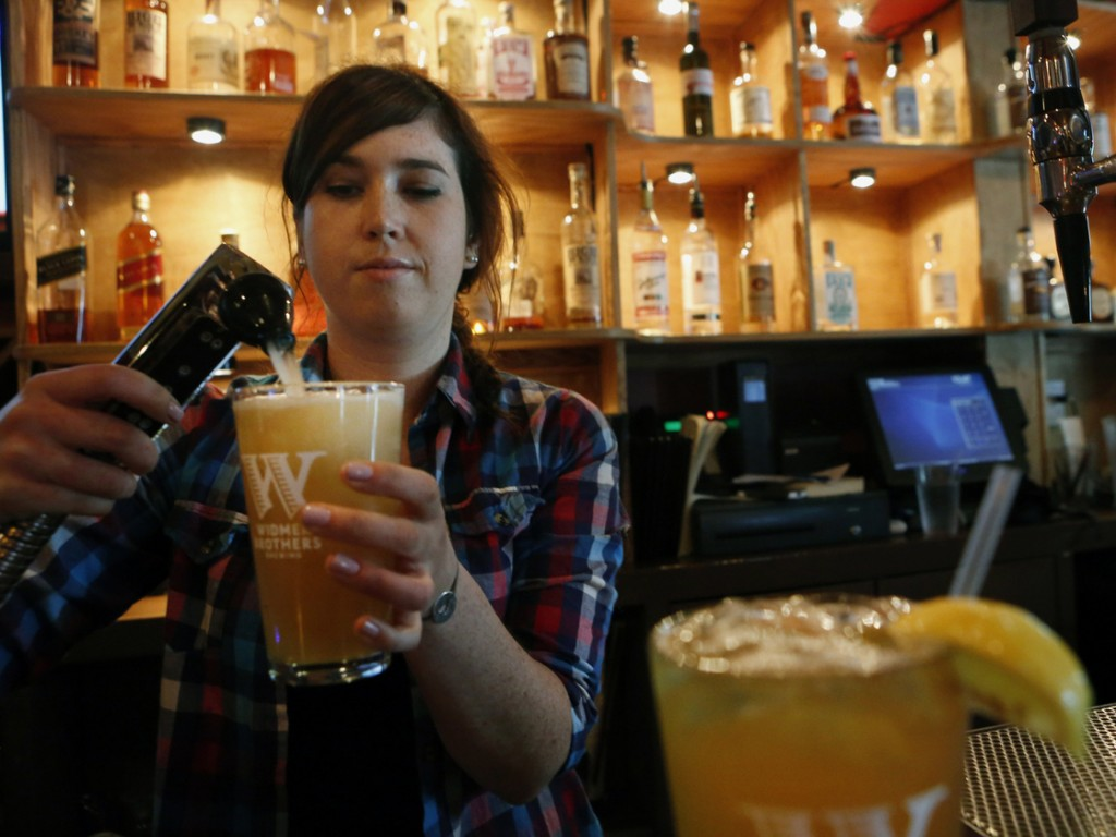 "Megan Horrigan mixes a shandy at Washington, D.C.'s Union Pub.""It's refreshing, great for the summer,"" says local customer Tom Tupa, who sampled the drink. Photo: Heather Rousseau/NPR"