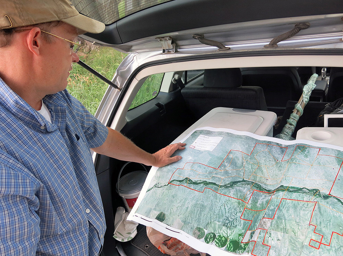 Ecologist William Burnidge checks a map of Fox Ranch that details the different areas rancher Nathan Andrews can graze his cattle. Photo: Luke Runyon/Harvest Public Media