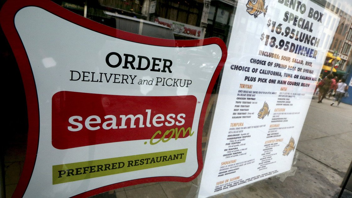 A Seamless sticker is displayed next to the menu in the window of a restaurant in New York's Times Square on Saturday. Rivals Seamless and GrubHub said Friday that they have completed their combination, creating an online takeout company covering about 25,000 restaurants in 500 cities. Photo: Mary Altaffer/AP