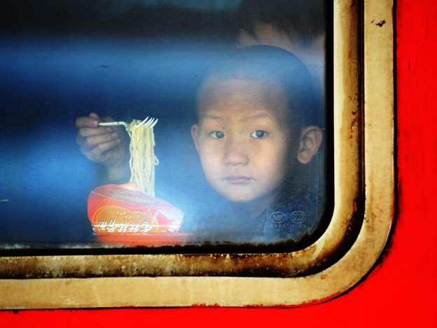 A child eats instant noodles on a train at the Harbin Railway Station in northeast China. Photo: WANG JIANWEI/Xinhua /Landov