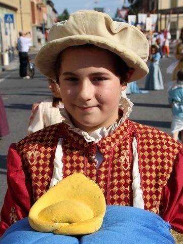 A young boy in Castelfranco Emilia, Italy, shows off a ceramic version of a tortellino during the town's annual celebration of the pasta's nameless inventor.