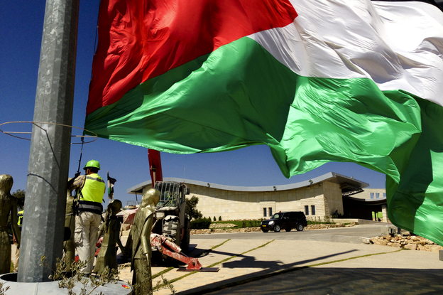 Palestinian flags at the top of Rawabi, where residents are planning to move in shortly. Photo: Emily Harris/NPR