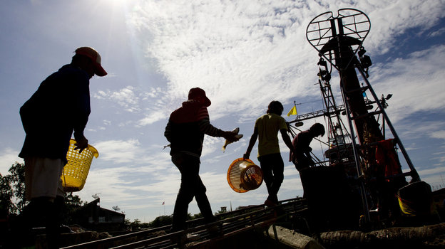 "Migrant workers from Myanmar return to a trawler after unloading fish following a fishing trip in the Gulf of Thailand in Samut Sakhon province Tuesday. A new report details ""deceptive and coercive"" labor practices in the Thai fishing sector, which relies heavily on workers from Cambodia and Myanmar, also known as Burma. Photo: Sakchai Lalit/AP"