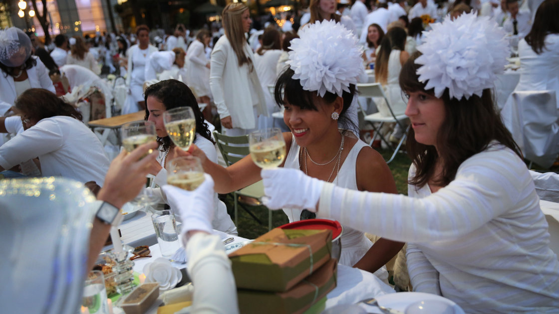 "At Diner en Blanc (""Dinner in White""), people arrive dressed all in white. They bring their own food and, fittingly,"" white wine. Photo: John Moore/Getty Images"