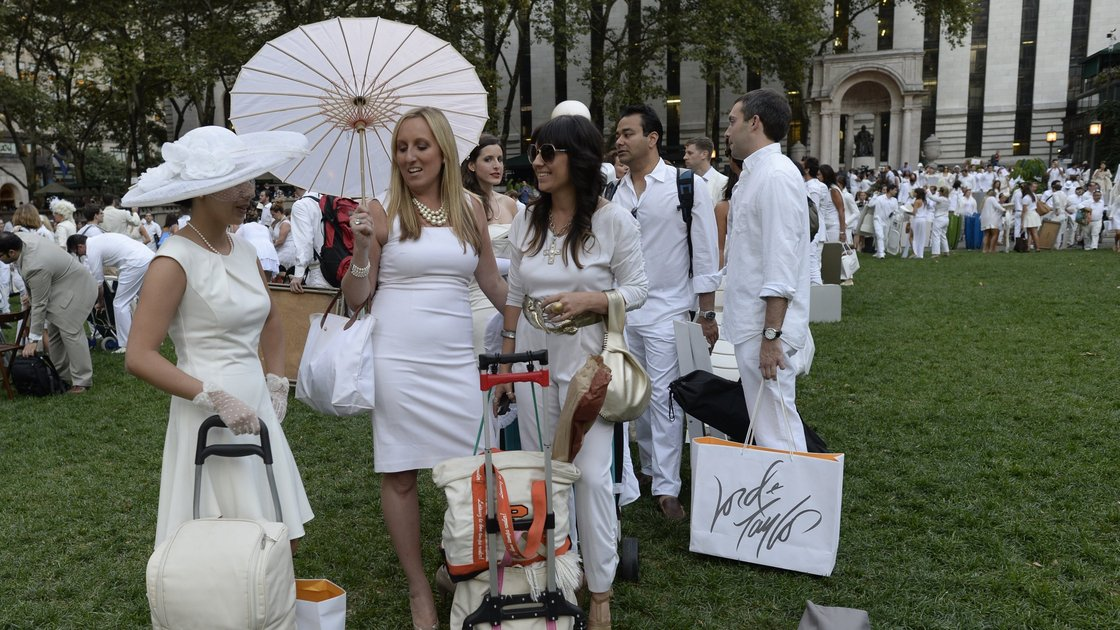 Guests arrive at Bryant Park last Wednesday, toting their dinner and dinnerware with them to the secret pop-up picnic. Photo: Timothy Clary/AFP/Getty Images