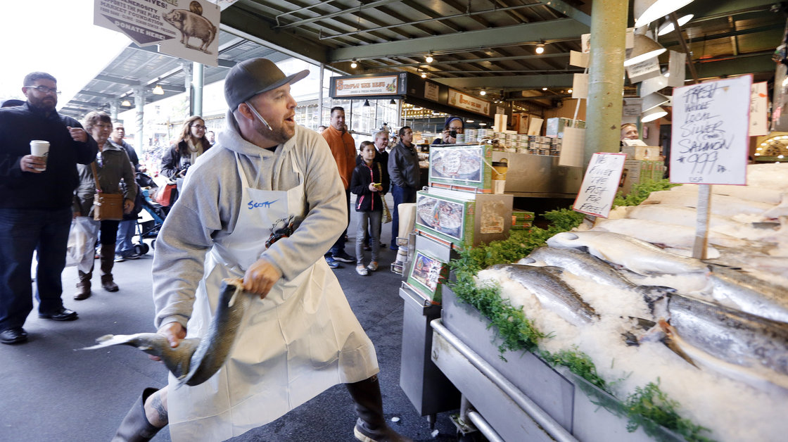 A fishmonger tosses a just-purchased fresh salmon to a colleague behind the counter at the Pike Place Fish Market in Seattle. Photo: Elaine Thompson/AP