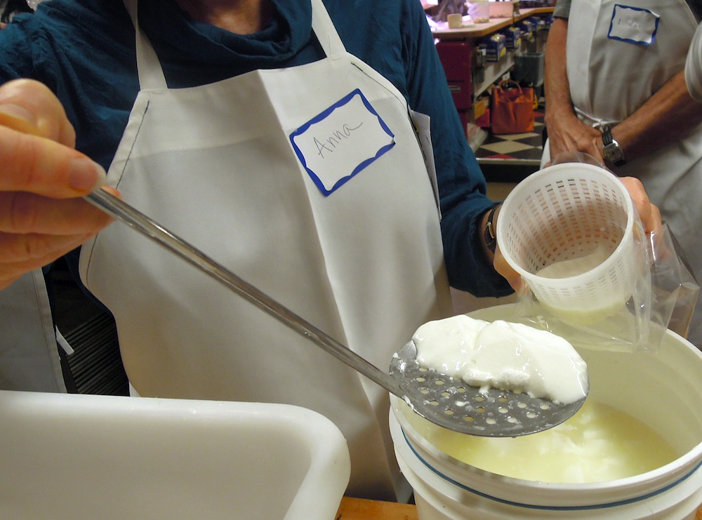Scooping the curds from the whey.