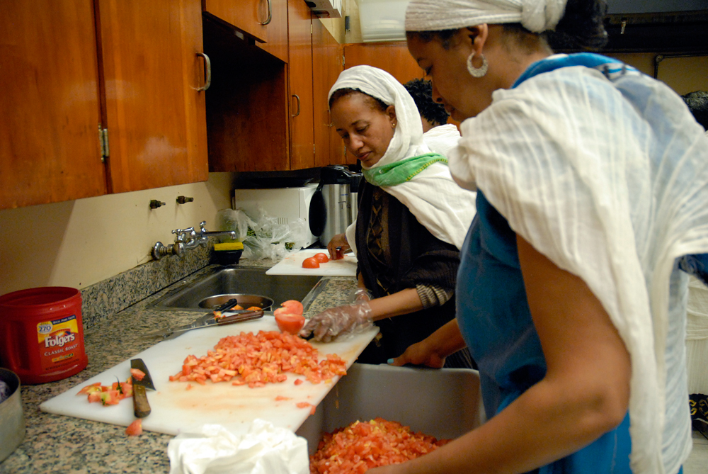 Women prep tomatoes for a salad in the church kitchen. Photo: Wendy Goodfriend