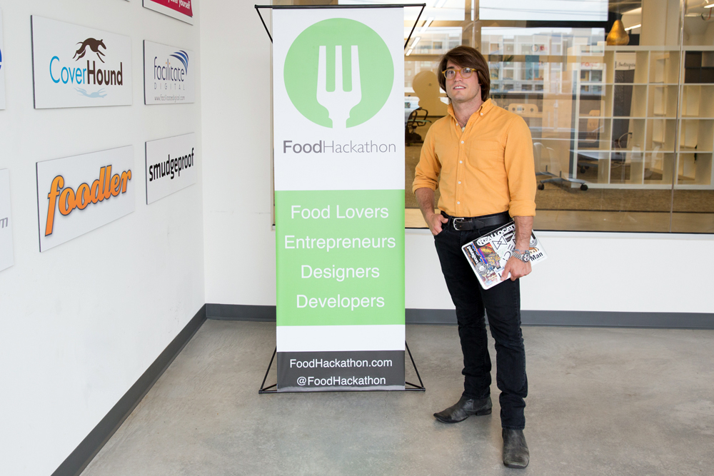 Tim West next to FoodHackathon signage. Photo courtesy of Molly DeCoudreaux