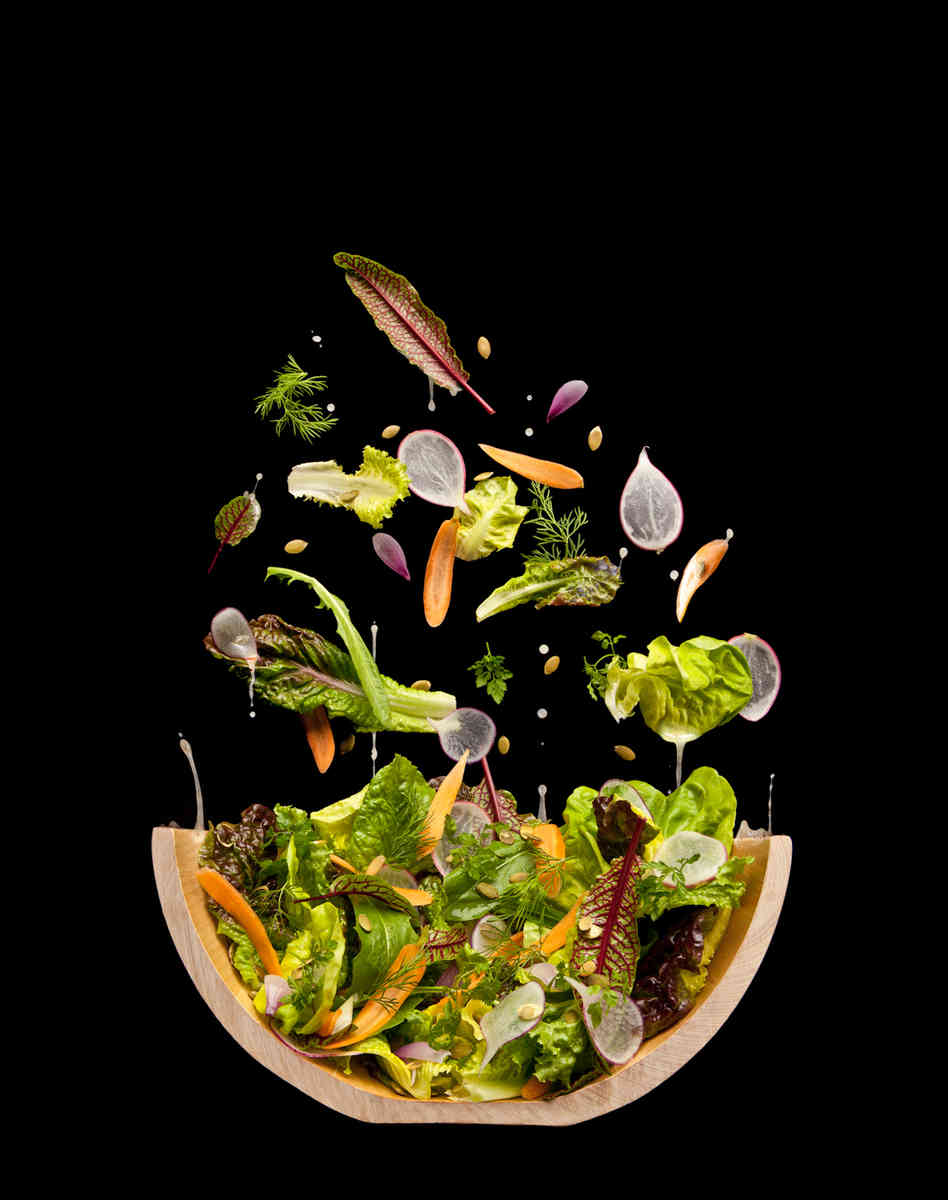 A tossed salad that isn't tossed. The photographers hung a piece of black velvet at a 70 degree angle and then pinned the leaves and nuts in place. Photo: Courtesy of The Cooking Lab