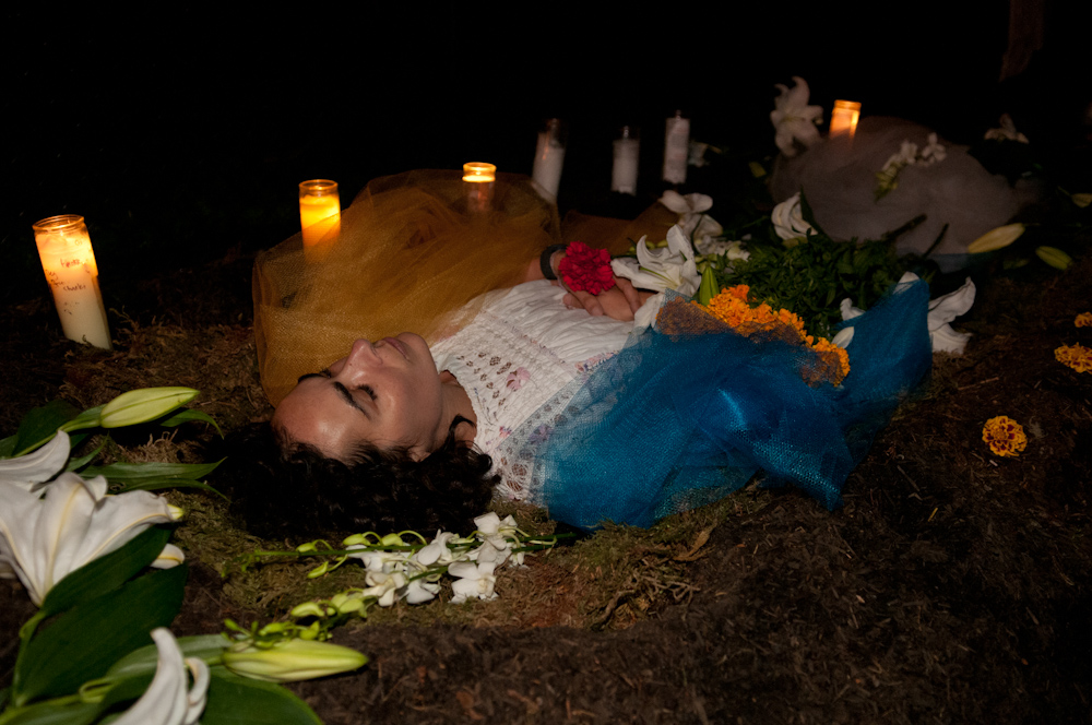 Performance piece: woman lying in grave. Photo: Naomi Fiss