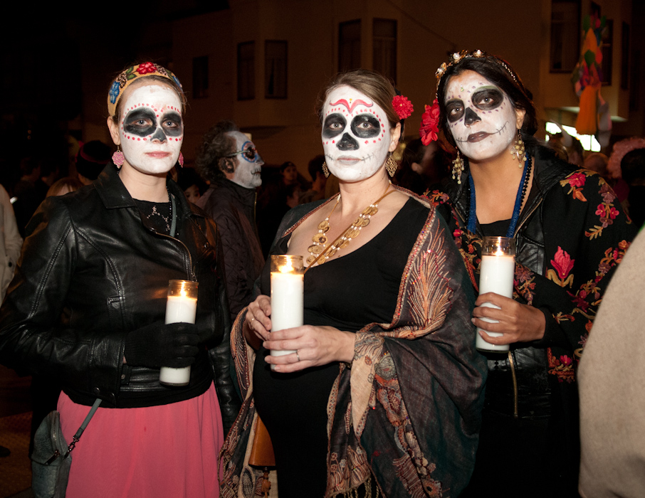 Three women during procession with memorial candles. Photo: Naomi Fiss