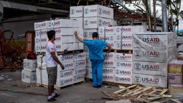 A relief worker looks over boxes of aid provided by the U.S. on November 14, 2013 in Leyte, Philippines. Proponents of food aid reform say it makes more sense for the U.S. to buy food donations locally than ship them across the globe. Photo: Chris McGrath/Getty Images